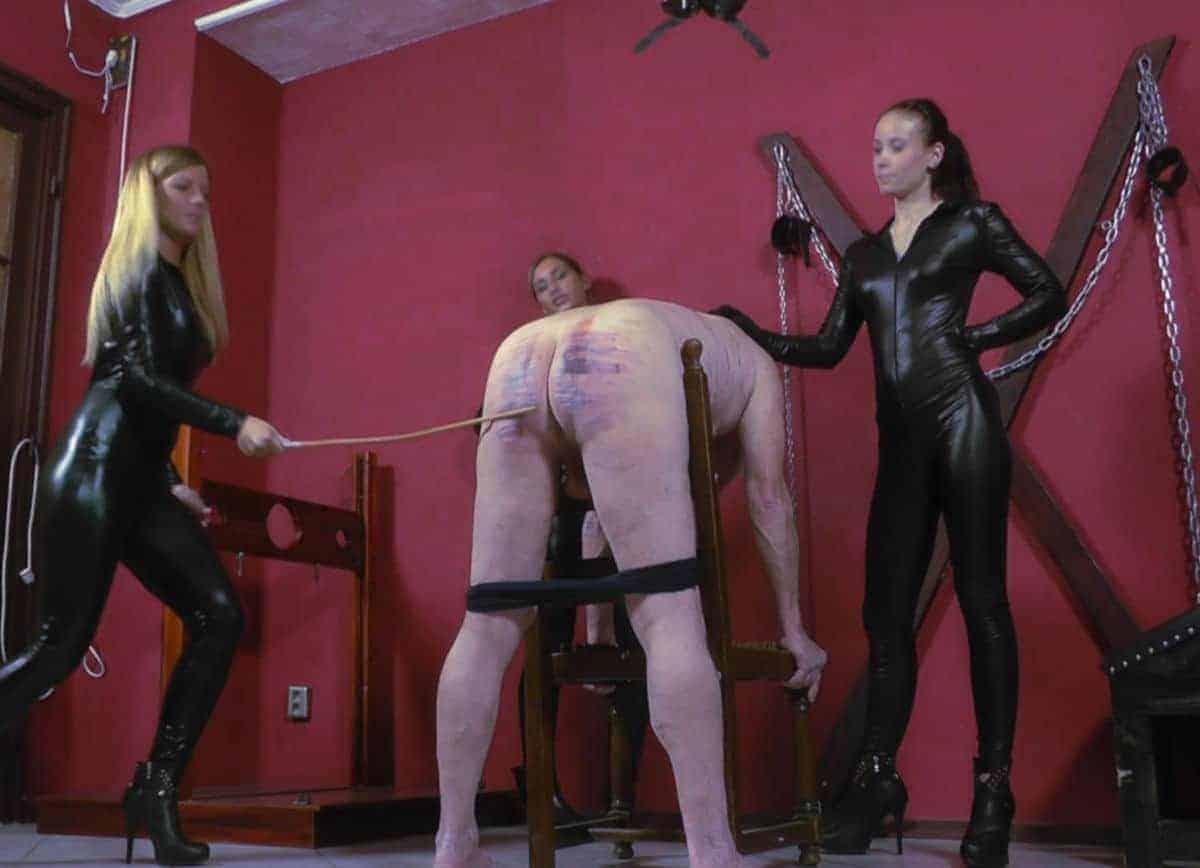 Domina qui punit son soumis par le bâton sous le regard d'une maîtresse complice